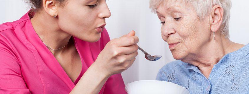 Nurse feeding an older lady