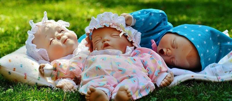 dolls lying on grass